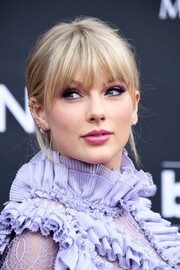 Taylor Swift sported a messy updo with eye-grazing bangs at the 2019 Billboard Music Awards.