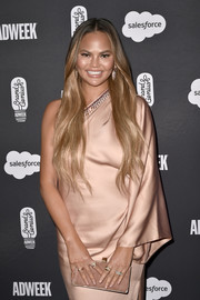 Chrissy Teigen matched a nude suede clutch by Jimmy Choo with a one-shoulder dress for the 2019 Brandweek Brand Genius Awards.