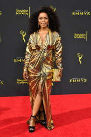 Angela Bassett added extra shimmer with a gold box clutch.