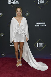 Jana Kramer attended the 2019 E! People's Choice Awards wearing a silver Kalmanovich fishtail dress with cape sleeves, bow detailing, and a plunging neckline.