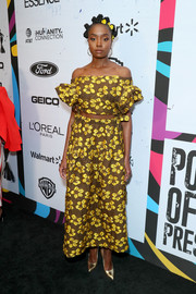 Kiki Layne sealed off her look with a pair of gold pumps.