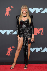 Heidi Klum complemented her dress with a black box clutch by Judith Leiber.