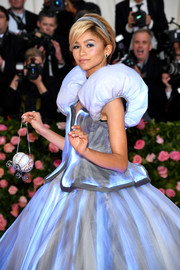 Zendaya Coleman, dressed as Cinderella, accessorized with an adorable pumpkin coach purse at the 2019 Met Gala.