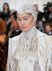 Gigi Hadid sported a sequined hat by Stephen Jones to match her coat and catsuit at the 2019 Met Gala.