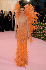 Kendall Jenner channeled her inner Vegas showgirl in a beaded orange Versace gown with a feathered collar, sleeve, and hem at the 2019 Met Gala.
