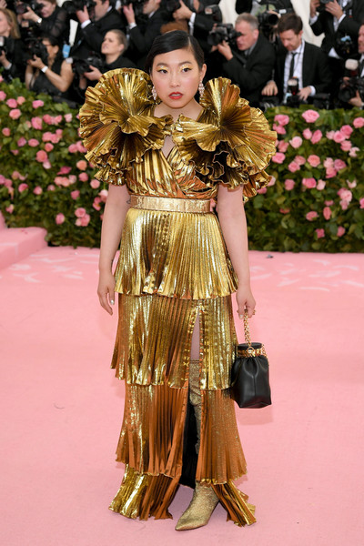 Awkwafina looked opulent in a tiered gold Altuzarra gown with statement ruffle sleeves at the 2019 Met Gala.