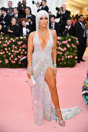 Jennifer Lopez flaunted her assets in a high-slit, deep-V halter gown by Atelier Versace at the 2019 Met Gala.