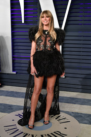Heidi Klum showed off her legs in a feathered fishtail dress by Elie Saab Couture at the 2019 Vanity Fair Oscar party.