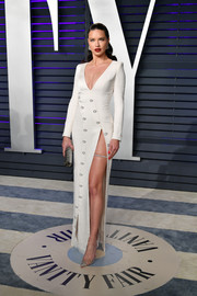 Adriana Lima pulled her look together with a silver tube clutch.