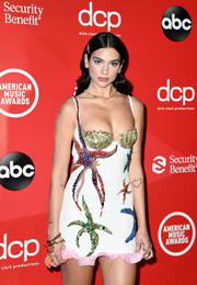 Dua Lipa complemented her embellished dress with a pair of gold charm bracelets for the 2020 American Music Awards.