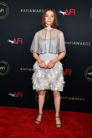 Thomasin McKenzie polished off her outfit with a sheer gray capelet.