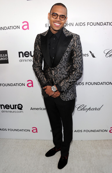 Chris Brown looked dapper in a classy leopard print blazer as he attended Elton John's Annual Academy Awards Viewing Party.