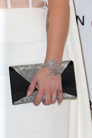 Kelly Osbourne spiced up her all-white look at Elton John's Oscar party with a black satin and crystal envelope clutch.