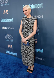 Michelle Williams paired her dress with black suede ankle-strap sandals.