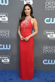 Olivia Munn chose a sleeveless red Prada gown with a beaded neckline and bodice for her 2018 Critics' Choice Awards look.