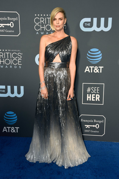 Charlize Theron looked downright glam in a silver Givenchy one-shoulder gown with a midriff cutout and an ombre skirt at the 2019 Critics' Choice Awards.