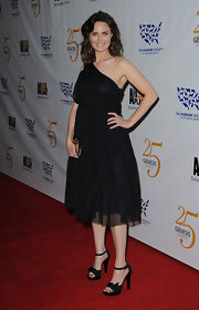 Emily Deschanel complemented her chiffon one shoulder dress with black satin ankle strap sandals.