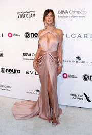 Alessandra Ambrosio amped up the allure at the Elton John AIDS Foundation Oscar-viewing party in a draped pink  Ralph & Russo Couture gown with a deep-V cutout, an open back, and a high slit.