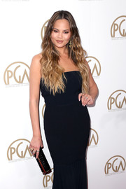 Chrissy Teigen paired a textured black tube clutch with a strapless dress for the Producers Guild Awards.