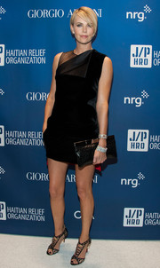 Charlize Theron completed her fiercely chic ensemble with a black Saint Laurent crocodile clutch.