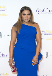 Mindy Kaling paired an embellished silver Nicoli clutch with a blue one-shoulder dress for the Gracie Awards.