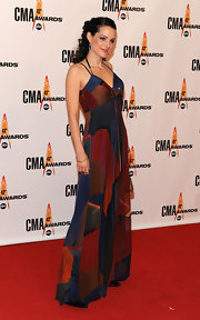 Kimberly wears a floor length maxi dress with a creative dark print and thin spaghetti straps to the CMA Awards.