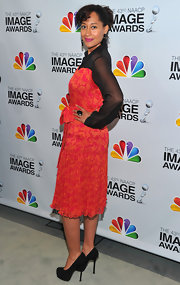 Tracee accessorized with black platform pumps.