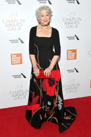 Helen Mirren added an extra pop of color with a red box clutch by Judith Leiber.