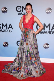 Hayley Orrantia looked like the goddess of spring during the CMA Awards in a floor-sweeping House of Ronald gown with a red lace bodice and a floral skirt.