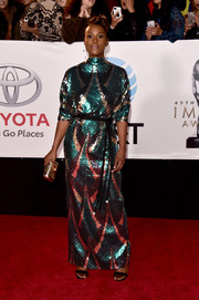 Issa Rae complemented her dress with a metallic gold clutch.