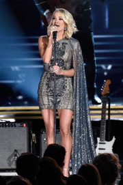 Carrie Underwood dazzled on stage in a sparkly Elie Madi one-shoulder mini dress with a floor-length side cape during the CMA Awards.