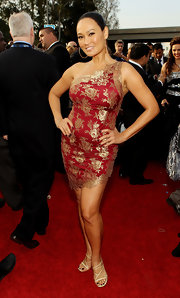 Tia Carrere paired nude strappy sandals with her red one-shoulder dress for a totally alluring look during the Grammys.