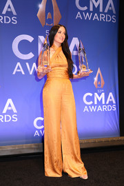 Kacey Musgraves hit the press room at the CMA Awards wearing an orange Cushnie jumpsuit with a crossover neckline.