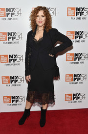 Bernadette Peters attended the New York Film Festival premiere of 'A Quiet Passion' wearing a black skirt suit with a lace-accented neckline, hem, and sleeves.