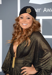Tamia showed her unique style through a flowing gold dress and matching black turban with gold brooch.