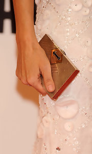 Here, Goya carries a gold metallic box clutch.