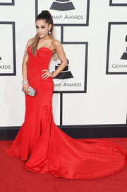 Ariana Grande made a head-turning entrance at the Grammys in a red Romona Keveza corset gown with a long train.