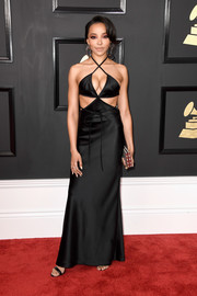Tinashe sizzled on the Grammys red carpet in a black Alexander Wang cutout dress with a cleavage-flaunting crisscross neckline that the singer wore with Atelier Swarovski jewelry.