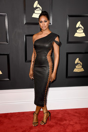 Laverne Cox was easily the center of attention as she hit the Grammys in a Bryan Hearns one-shoulder leather  dress with skin-revealing side panels.