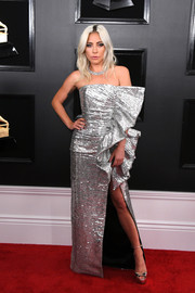 Lady Gaga looked radiant in a strapless silver gown with a high slit and ruffle detailing at the 2019 Grammys.