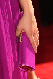 This tube clutch by Jimmy Choo has gold hardware.