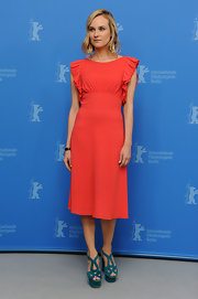 Diane Kruger added wow factor to her coral dress with suede turquoise platform sandals.