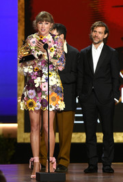 Taylor Swift cut a sweet figure in a floral-appliqued cocktail dress by Oscar de la Renta at the 2021 Grammy Awards.