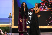 H.E.R. looked exotic in an embroidered purple velvet dress layered over coordinating pants at the 2021 Grammy Awards.