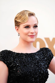 For the 63rd Emmys, Evan Rachel Wood's hair was styled in an exaggerated finger wave. The super sleek look can be achieved by applying a product like Bumble and Bumble Gel throughout slightly damp hair, making a deep side part and sweeping tresses over and across the forehead into a 'c' shape. In the middle of the 'c', insert a three and a half inch long aluminum curler clip, turning the 'c' into an 's' shape. Allow hair to dry, remove clip and mist with hairspray.