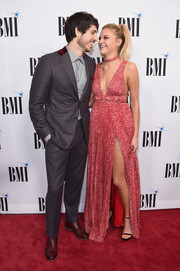 Kelsea Ballerini looked daring in a red Amur empire gown with a plunging neckline and a high side slit at the BMI Country Awards.