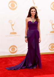 Thea's plum-colored draped strapless dress flowed gracefully on the red carpet.