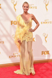 Heidi Klum flashed her long, lean legs at the Emmy Awards in a one-sleeve yellow Atelier Versace gown with a see-through skirt and a ruffled and appliqued bodice.