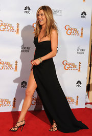 Jennifer Aniston donned strappy black sandals with her sexy leg-baring gown.