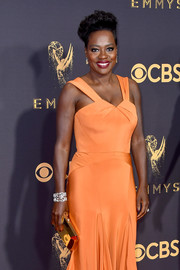 Viola Davis paired a mirrored gold clutch by Tyler Ellis with an orange evening dress for the 2017 Emmys.